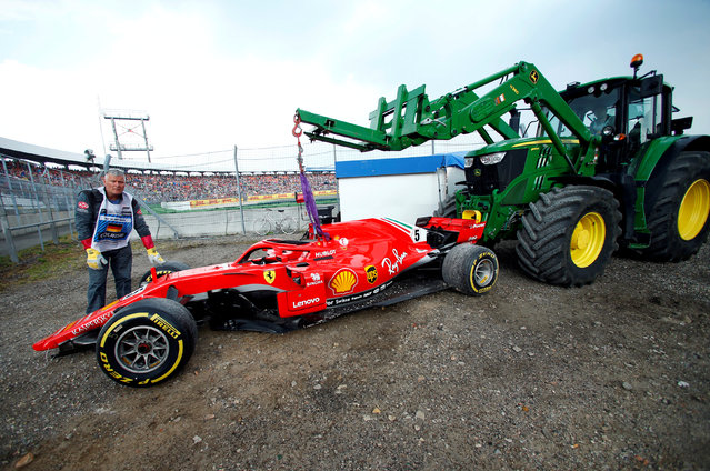 Staff members help as a tractor lifts the car of Ferrari' s German driver Sebastian Vettel during the German Formula One Grand Prix at the Hockenheim racing circuit on July 22, 2018 in Hockenheim, southern Germany. (Photo by Ralph Orlowski/Reuters)