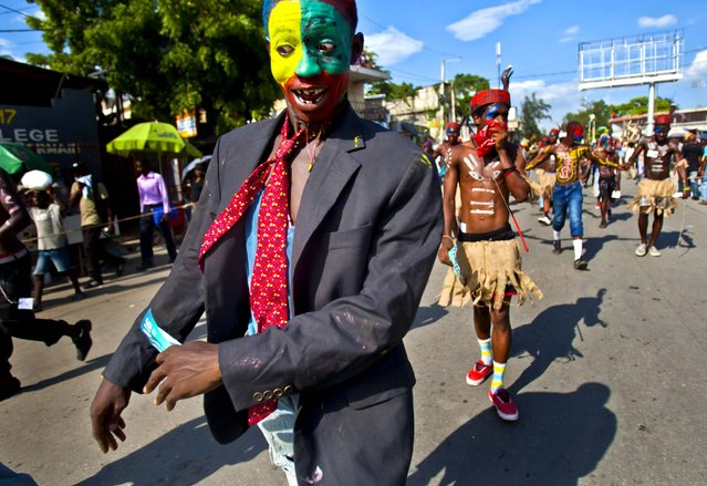 """Revelers march in the """"Carnival of Flowers"""" parade in Port-au-Prince, Haiti, on July 29, 2013. Tens of thousands of people poured into downtown Port-au-Prince for the Caribbean nation's second """"Carnival of Flowers"""", a three-day celebration President Michel Martelly has revived from the Duvalier era. (Photo by Dieu Nalio Chery/Associated Press)"""