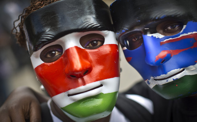 Protesters wear masks, the left in the colors of the Kenyan national flag, as they join others carrying mock coffins and red-painted crosses, symbolizing the blood of the 28 non-Muslims singled out and killed in the recent attack on a bus in Mandera by Somali militant group al-Shabab, outside government offices in downtown Nairobi, Kenya Tuesday, November 25, 2014. (Photo by Ben Curtis/AP Photo)