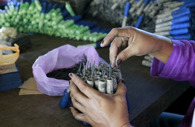 A worker adds wicks to fireworks inside a shanty in Bocaue town, Bulacan province, Philippines, December 26, 2015. (Photo by Romeo Ranoco/Reuters)