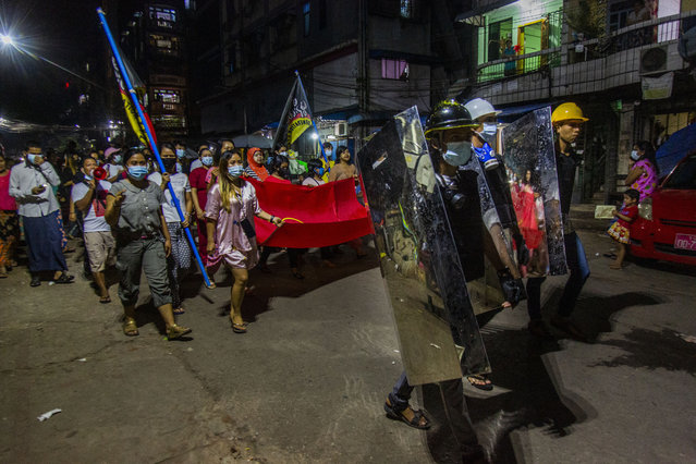 Residents march around their neighborhood despite an overnight curfew in an anti-coup night rally at the Myaynigone area of Sanchaung township in Yangon, Myanmar Monday, March 15, 2021. Myanmar's ruling junta has declared martial law in a wide area of the country's largest city Yangon, as security forces killed dozens of protesters over the weekend in an increasingly lethal crackdown on resistance to last month's military coup. (Photo by AP Photo/Stringer)