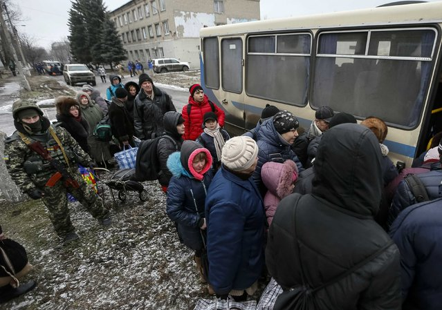 A member of the Ukrainian armed forces assists local residents onto a bus to flee the military conflict, in Debaltseve, eastern Ukraine, February 6, 2015. (Photo by Gleb Garanich/Reuters)