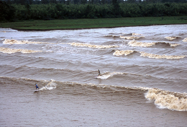 Surfers Adilton Mariano and Rodrigo Resende ride the Pororoca wave in the Araguari river in northern Brazil, on May 18, 2003. (Photo by Enrico Marone/AP Photo via The Atlantic)