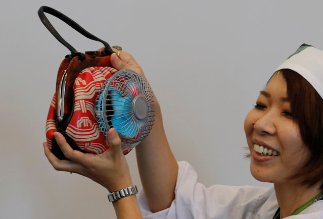 Japanese graphic designer Tanago Akiko demonstrates her creation, the prototype of Fan-Handbag during the Underground Maker Festival in Tokyo, Japan August 5, 2018. Tanago Akiko said she created this handbag which has a small fan outside of the bag as a measurement for the heat wave. (Photo by Kim Kyung-Hoon/Reuters)
