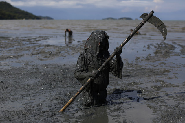 "A mud covered reveler wearing a grim reaper costume enjoys the traditional ""Bloco da Lama"" or ""Mud Block"" carnival party, in Paraty, Brazil, Saturday, February 14, 2015. (Photo by Leo Correa/AP Photo)"