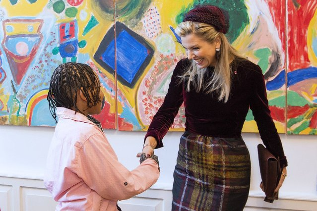 Queen Maxima of the Netherlands (R) shakes hands with a child during a visit to the Vitalis non-profit organisation in The Hague on November 29, 2016. (Photo by Frank van Beek/AFP Photo/ANP)