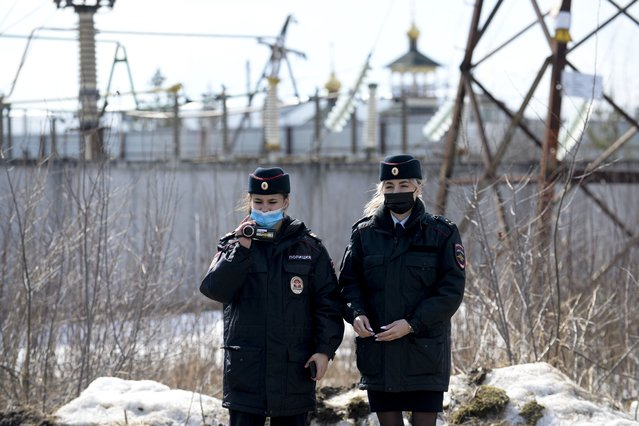 Police officers film as the Alliance of Doctors union's leader Anastasia Vasilyeva speaks to the media at the prison colony IK-2, which stands out among Russian penitentiary facilities for its particularly strict regime, in Pokrov in the Vladimir region, 85 kilometers (53 miles) east of Moscow, Russia, Tuesday, April 6, 2021. (Photo by Denis Kaminev/AP Photo)