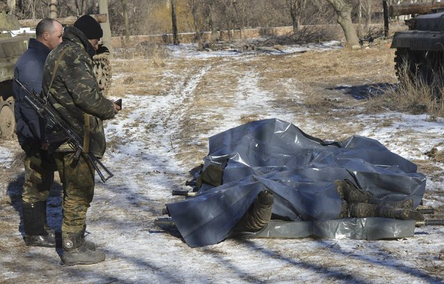 Ukrainian soldiers stand next to bodies of their comrades killed in Debaltseve at a military camp in Artemivsk, February 18, 2015. (Photo by Oleksandr Klymenko/Reuters)