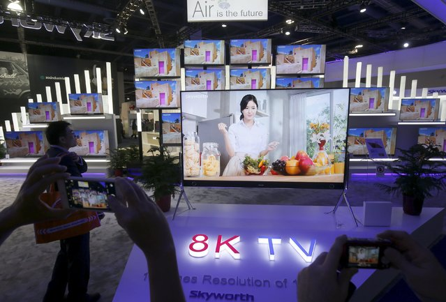 People take photos of a prototype 98-inch, 8K television at the Skyworth booth during the 2016 CES trade show in Las Vegas, Nevada January 8, 2016. One of the top three television manufacturers in China, the company hopes to enter into the U.S. market in late 2016, a representative said. (Photo by Steve Marcus/Reuters)
