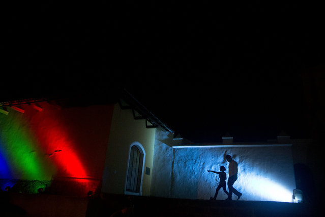 A man and child are silhouetted against the wall of the San Francisco Convent as they leave an event where a symbolic burial of violence took place, organized by the International Poetry Festival of Granada, in Granada, Nicaragua on Wednesday, February 18, 2015. Organizers said more than 100 poets from around the world are expected to participate in the week-long festival. (Photo by Esteban Felix/AP Photo)