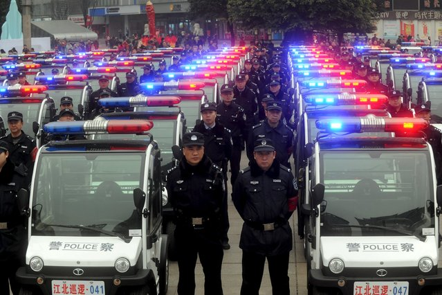 People watch a police force showcase during the debut of new patrolling police vehicles in Chongqing Municipality, China, January 18, 2016. (Photo by Reuters/Stringer)