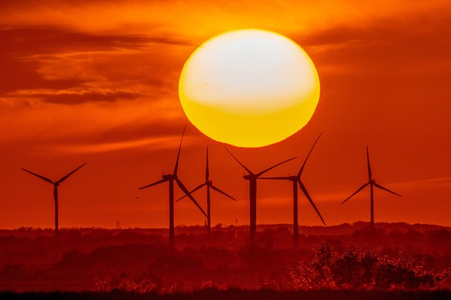 The sun setting over Tick Fen wind farm in Cambridgeshire, a county in the East of England on Wednesday evening, May 5, 2021. (Photo by Bav Media)