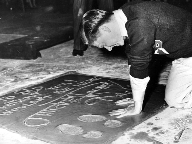 Mickey Rooney, 18-year-old film actor, singer and dancer, plants his hands into the cement next to his footprint and signature in the forecourt of Grauman's Theater on Hollywood Boulevard during induction ceremonies in Hollywood, Ca., on October 19, 1938. (Photo by AP Photo)