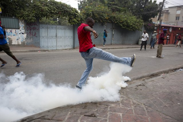 A demosntrator kicks a canister of tear gas during a street protest after it was announced that the runoff Jan. 24, presidential election had been postponed, in Port-au-Prince, Haiti, Friday, January 22, 2016. (Photo by Dieu Nalio Chery/AP Photo)