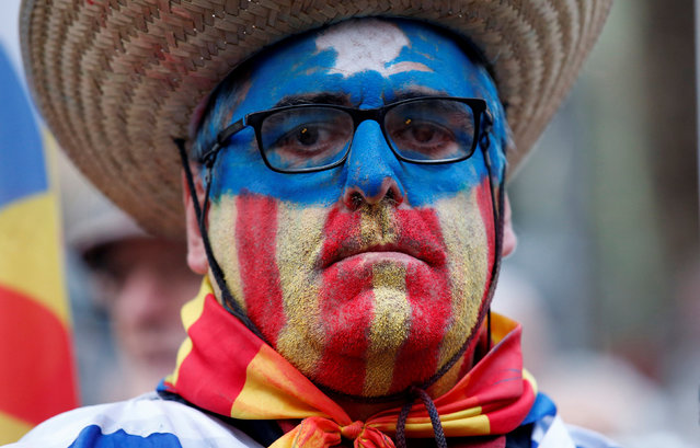 A supporter of Catalunya Parliament's President Carme Forcadell, with an estelada (Catalan separatist flag) painted on his face, is pictured in front of the court in Barcelona, Spain, December 16, 2016. (Photo by Albert Gea/Reuters)