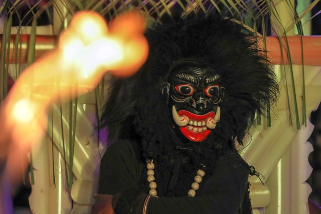 """A Sri Lankan traditional dancer wearing a devil mask performs during  the traditional exorcismritual """"Daha Ata Sanniya"""" ritualistic festival in Kaluthara outskirt of Colombo, Sri Lanka, 18 April 2021. Also known as """"Daha Ata Sannia"""" or """"Sanni Yakuma"""", it is a traditional exorcism ritual of Sinhala Buddhists on the southern coast and in the western parts of Sri Lanka. It is usually held with the intention of healing a sick person who is believed to be possessed by a demon. The ritual consists of 18 masks, which represent specific diseases or ailments that affect people. This ritual is performed today as a cultural spectacle rather than an exorcism ritual. However, due to its high cost and its longevity, it is not widely used. (Photo by Chamila Karunarathne/EPA/EFE)"""