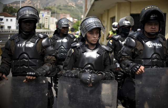 Colombian riot police guard a march in Cali, Colombia, on January 24, 2016. Thousands take to the streets to demand an increase in the minimum wage and protest the economic policies of Colombian President Juan Manuel Santos. (Photo by Luis Robayo/AFP Photo)
