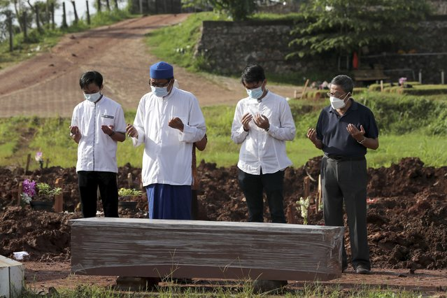 An Islamic cleric leads relatives in prayer during the burial of a man in the special section of Jombang Public Cemetery reserved for those who died of COVID-19, in Tangerang on the outskirts of Jakarta, Indonesia, Monday, June 21, 2021. Indonesia saw significant spikes in confirmed COVID-19 cases recently, an increase blamed on travel during last month's Eid al-Fitr holiday as well as the arrival of new virus variants, such as the the Delta version first found in India. (Photo by Tatan Syuflana/AP Photo)