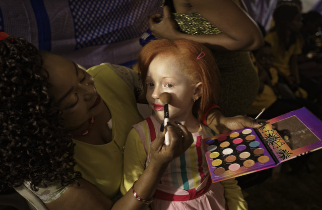 Elsie Lynn, 6, has her makeup done a she waits for the start of the Mr. & Miss Albinism East Africa contest, organized by the Albinism Society of Kenya, in Nairobi, Kenya Friday, November 30, 2018. (Photo by Ben Curtis/AP Photo)