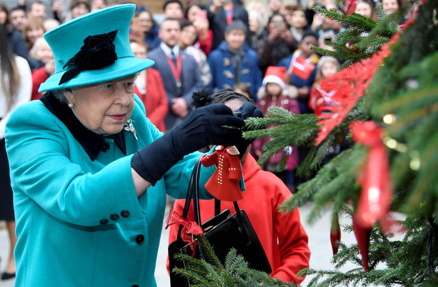 Britain's Queen Elizabeth and Shylah Gordon, aged 8, attach a bauble to a Christmas tree during a visit to children's charity Coram in London, Britain, December 5, 2018. (Photo by Toby Melville/Reuters)