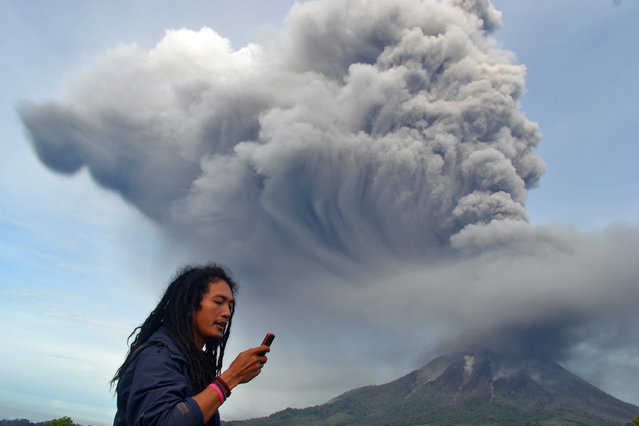 A man uses his mobile phone as Mount Sinabung continues to erupt, with hot smoke spewing from the volcano, in the Karo district on the north of Indonesia's Sumatra island on November 18, 2013. Officials said a week ago at more than 5,000 people had fled their homes since the volcano erupted early this month. (Photo by Sutanta Aditya/AFP Photo)