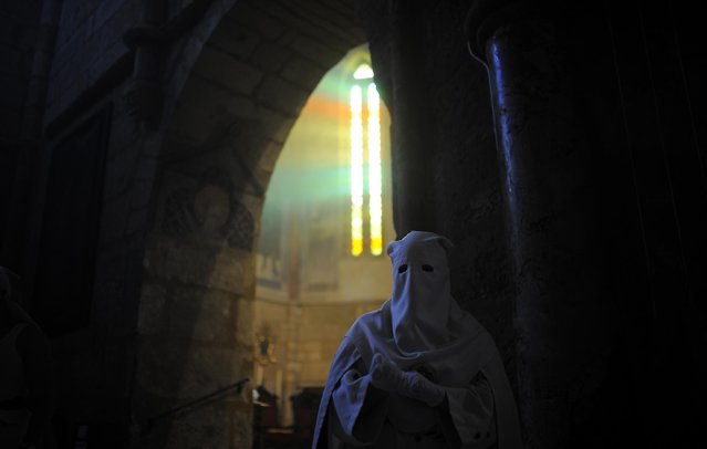 """A hooded penitent from """"La Borriquita"""" brotherhood takes part during a Holy Week procession in Cordoba, Spain, Sunday, March 29, 2015. (Photo by Manu Fernandez/AP Photo)"""