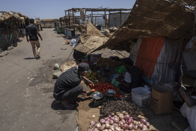 Tigrayan refugee Abraha Kinfe Gebremariam, 40, buys tomatoes at the market in Hamdayet, eastern Sudan, near the border with Ethiopia, on March 21, 2021. One day during the conflict in his home village, his son, Daniel, tried to visit the market and saw some 10 bodies being piled onto a vehicle for burial. He saw another four bodies in the dirt. Daniel never went to the market again. (Photo by Nariman El-Mofty/AP Photo)
