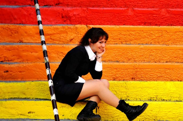 A woman poses on rainbow-colored stairs in Istanbul on November 19, 2013. (Photo by Ozan Kose/AFP Photo)