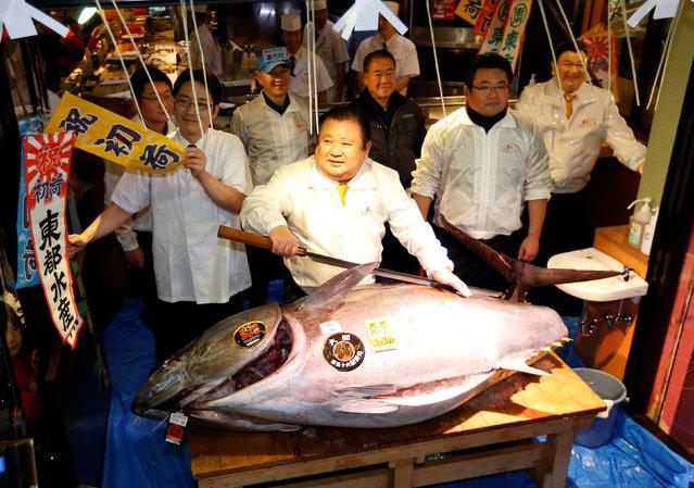 Kiyomura Co's President Kiyoshi Kimura (C), who runs a chain of sushi restaurants Sushi Zanmai, holds a sword as he poses with a 212 kg (467 lbs) bluefin tuna at his sushi restaurant outside Tsukiji fish market in Tokyo, Japan, January 5, 2017. (Photo by Issei Kato/Reuters)