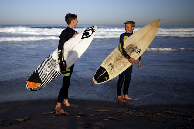Reid Inskeep, 13, (R) and Luke Personius, 12, walk out of the ocean after surfing before school at sunrise in Hermosa Beach, California April 2, 2015. (Photo by Lucy Nicholson/Reuters)