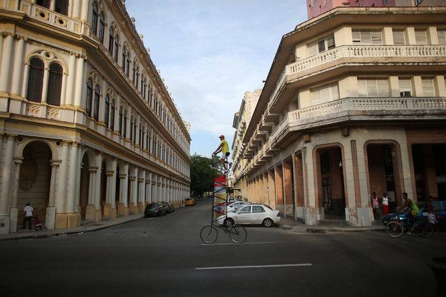 Felix Guirola, 52, rides a homemade bike with an advertising banner in Havana, Cuba, July 20, 2016. (Photo by Alexandre Meneghini/Reuters)