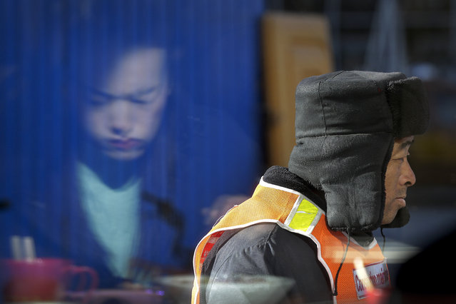 A construction worker walks by a woman eating her lunch as she is reflected on a restaurant's window in Beijing, Tuesday, January 15, 2019. China plans to slash taxes, step up spending and provide ample financing to private and small enterprises to help counter the country's worst slowdown since the global financial crisis and the impact of a bruising trade war with the U.S. (Photo by Andy Wong/AP Photo)