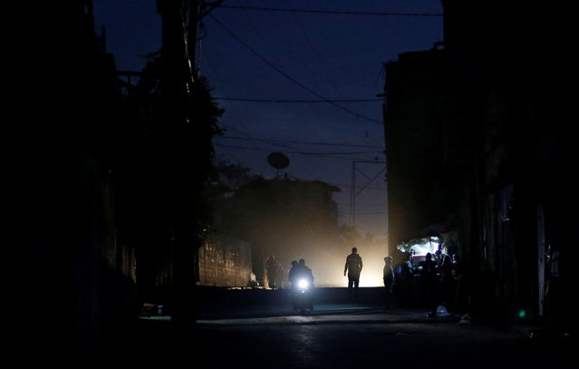 Palestinians ride a motorcycle during a power cut on a street in Beit Lahiya in the northern Gaza Strip January 11, 2017. (Photo by Mohammed Salem/Reuters)