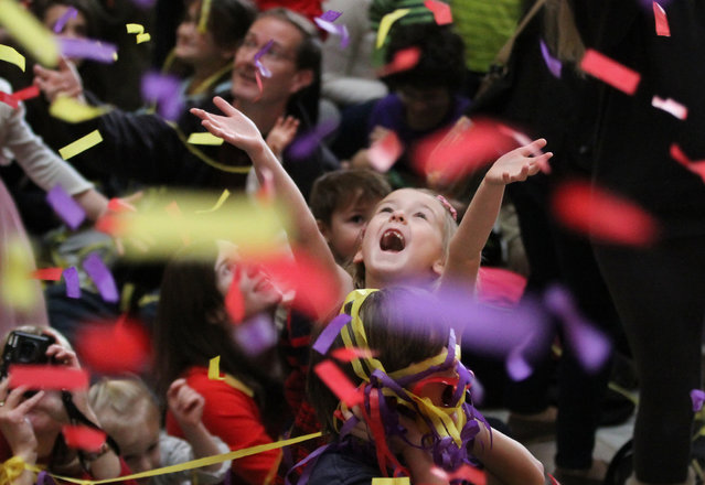 Cora Murphy-Usher, 7, of Narberth, Pa. is totally captivated by the streaming confetti coming down from the sky inside the Please Touch Museum as she and hundreds more, celebrated the New Year at noon on Tuesday, December 31, 2013 in Philadelphia. (Photo by Michael Bryant/AP Photo/The Philadelphia Inquirer)