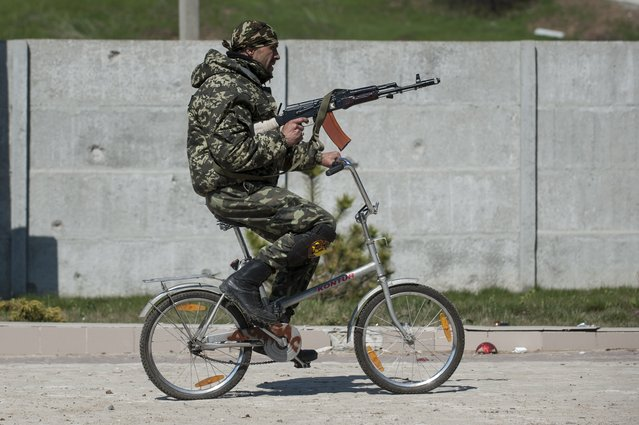 A Ukrainian serviceman rides a bicycle in Shyrokyne, eastern Ukraine, Wednesday, April 15, 2015. Russia and Ukraine agreed in Berlin on Monday to call for the pullback of smaller-caliber weapons from the front lines of the conflict that has claimed more than 6,000 lives. (Photo by Evgeniy Maloletka/AP Photo)