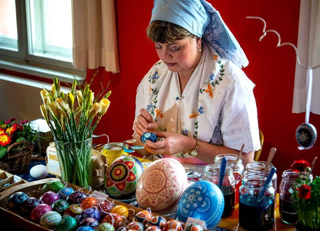 Martina Riedel in traditional sorbisch-wendisch dress, decorating eggs in the Spreewald-Museum in Luebbenau, Germany, 27 February 2016. The 17th easter egg fair was opened today at the museum. (Photo by Patrick Pleul/AP Images/DPA)