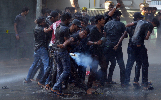 Sri Lankan Higher National Diploma student throws a tear gas canister back towards the police during clashes in a protest march demanding better conditions at state-run universities, in Colombo on February 26, 2019. (Photo by Ishara S. Kodikara/AFP Photo)