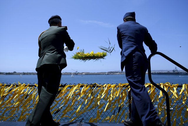 Former Vietnamese military men throw a memorial reef off the deck of the USS Midway as the ship hosts a day-long ceremony commemorating the 40th Anniversary of Operation Frequent Wind and the fall of Saigon in San Diego, California, United States April 26, 2015. (Photo by Mike Blake/Reuters)