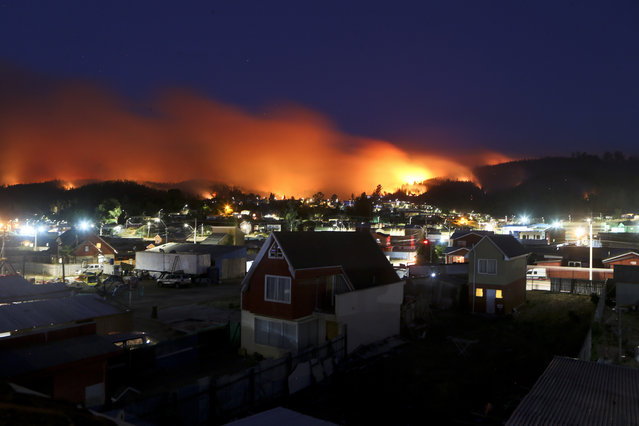 In this Monday, January 30, 2017 photo, wildfires straddle Chile's Dichato community. Strong winds are continuing to stoke the flames of raging wildfires in Chile, forcing the evacuation of more than 800 families in the coastal town of Dichato. (Photo by Esteban Felix/AP Photo)