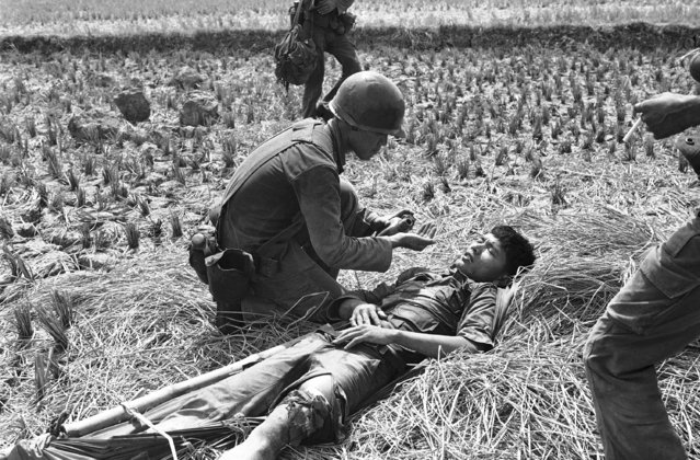 A South Vietnamese medic comforts a trooper wounded in the leg during a battle in Long An province southwest of Saigon on April 18, 1975. Fighting in the area, just north of the Mekong Delta, is on the increase. (Photo by AP Photo/Rocco)