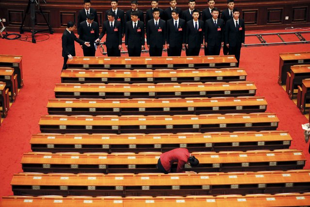 Security agents stand guard as an attendant searches delegates' desks after the closing ceremony of the Chinese People's Political Consultative Conference (CPPCC) at the Great Hall of the People in Beijing, China, March 14, 2016. (Photo by Damir Sagolj/Reuters)