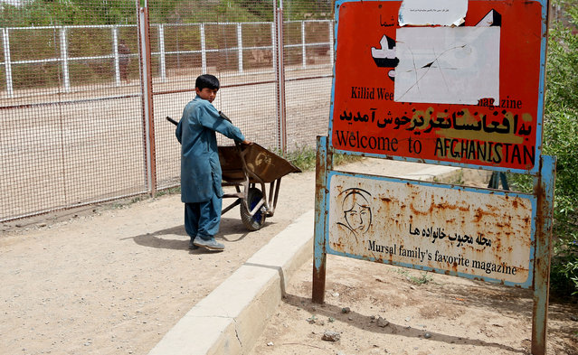 In this Monday, April 13, 2015 photo, an Afghan child laborer pushes a cart, at the Afghanistan-Iranian border point on the outskirts of Islam Qala in Herat province, west of Kabul, Afghanistan. (Photo by Massoud Hossaini/AP Photo)