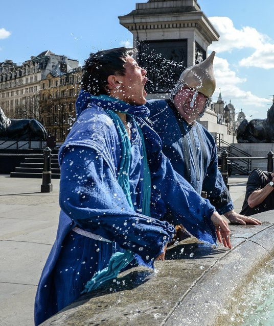 "One of Jesus' disciples is dunked in a fountain during The Wintershall's ""The Passion of Jesus"" in front of crowds on Good Friday at Trafalgar Square on March 25, 2016 in London, England. (Photo by Chris Ratcliffe/Getty Images)"