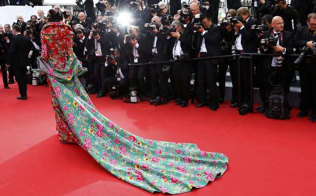 """An unidentified guest poses on the red carpet as she arrives for the opening ceremony and the screening of the film """"La tete haute"""" out of competition during the 68th Cannes Film Festival in Cannes, southern France, May 13, 2015. (Photo by Yves Herman/Reuters)"""