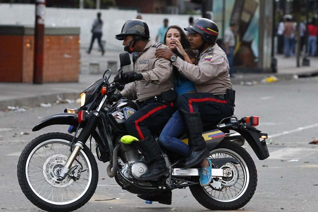 An anti-government protester is detained by police during clashes with police at Altamira square in Caracas March 6, 2014. A Venezuelan soldier and a motorcyclist died in a confused melee sparked by the opposition's barricading of a Caracas street, officials said on Thursday, boosting the death toll from nearly a month of violence to 20. Demonstrators have for weeks staged rallies and set up barricades to demand the resignation of President Nicolas Maduro, leading to clashes with security forces and government supporters. (Photo by Carlos Garcia Rawlins/Reuters)