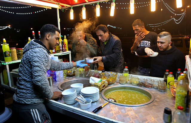 In this February 13, 2019 photo, a chickpea soup vendor serves customers at a roadside stand, Tahrir Square, in Baghdad, Iraq. For the first time in years, Iraq is not at war. The defeat of the Islamic State group in late 2017 after a ruinous four-year conflict has given the population a moment of respite, and across the capital Baghdad there is a guarded sense of hope. (Photo by Khalid Mohammed/AP Photo)