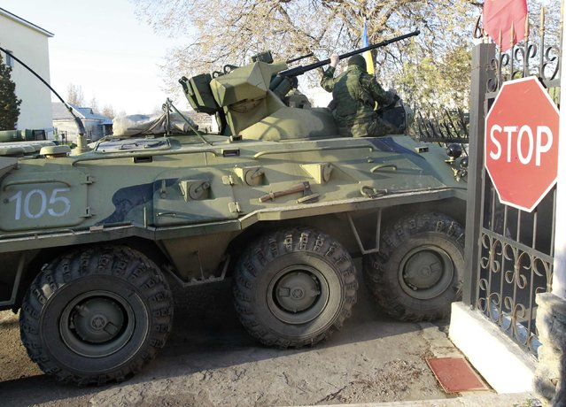 Armed men, believed to be Russian servicemen, drive an armoured vehicle onto the territory of a military airbase as they attempt to take over in the Crimean town of Belbek near Sevastopol March 22, 2014. (Photo by Shamil Zhumatov/Reuters)