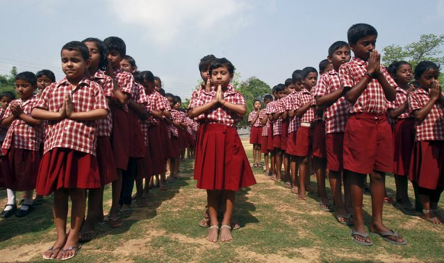 School children pray for the victims of a fire at a temple in the southern state of Kerala in the lawns of their school in Agartala, India, April 11, 2016. (Photo by Jayanta Dey/Reuters)