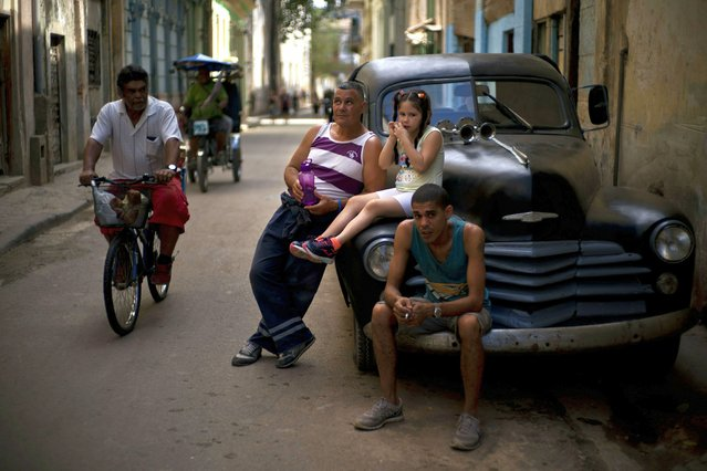 People rest on a classic American car as a man pedals his bike past in Havana, Cuba, Wednesday, April 10, 2019. (Photo by Ramon Espinosa/AP Photo)
