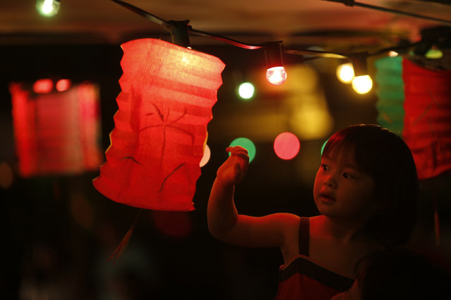A girl touches a lantern at an outdoor restaurant during the Chinese Mid-Autumn Festival in Hong Kong Sunday, September 30, 2012. Like ancient Chinese poets, Hong Kong people appreciate the beauty of the full moon in the Mid-Autumn Festival. (Photo by Vincent Yu/AP Photo)